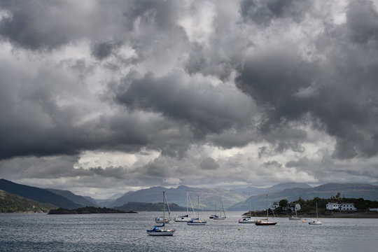 Sailboats on Kyle Akin straight to Loch Alsh at Kyleakin Isle of Skye with Caisteal Maol and dark clouds Scottish Highlands Scotland