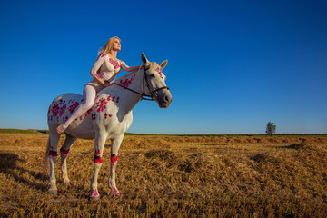 Blonde girl in white and red bodypaint jumps over the field with a white horse  Wall mural