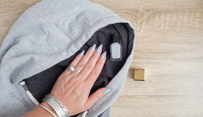 A female hand with long nails holds a bottle with a grey nail polish