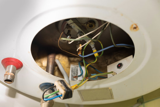 Inside of the broken water heater or boiler with electric wires and pipes for installation of the hoses with rust and burn selective focus close up