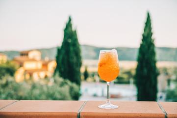 Refreshing aperol spritz cocktails with sliced orange. Tuscany landscape on background