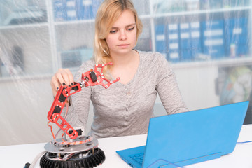 Young attractive female engineer working on robotics project