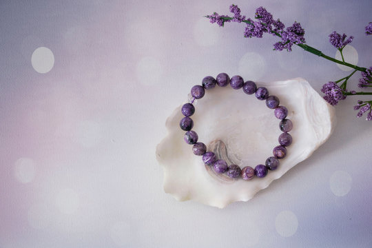 An close-up of an amethyst bracelet on a seashell next to a purple flower with a purple and white bokeh background.