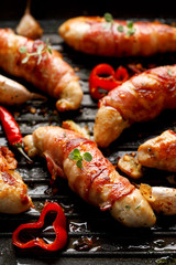 Spicy chicken meat, Grilled chicken tenderloin wrapped with bacon with addition chili peppers, garlic and herbs on grill plate, close-up top view