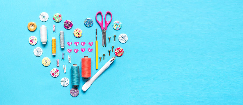 sewing thread set of sewing supplies in knolling pattern on light blue background flat lay top view, template mockup hand made long banner