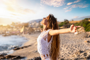 Junge, blonde Frau streckt ihre Arme am Strand aus und genießt die Freiheit und Ruhe