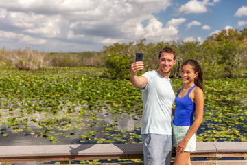 Wall Mural - Florida travel tourists couple taking selfie photo at Everglades National park walking in wetlands Anhinga trail walkway boardwalk summer tourism lifestyle young people.
