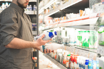Fototapeta Man in a shirt with two bottles of yogurt in his hands. Buyer is buying a dairy product in a supermarket. Hands of a man with milk close up, background of a light refrigerator with shelves. Copyspace obraz