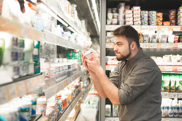 Funny man with a beard is in the milk department of the supermarket near the shelves of yogurt,holds in his hands yogurt and looks hungry look. Hungry man chooses yogurt in a supermarket.