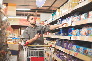 Buyer with a cart stands in the aisle supermarket sweets department, holds a smartphone in his hands and takes the goods out of the shelf. Man with a beard buys food in a supermarket.
