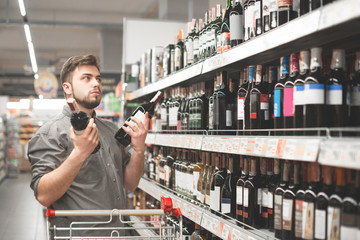 Buyer with a cart stands in the alcohol department of the supermarket near the shelves with wine,holds two bottles of wine in his hands,chooses what to buy.Man chooses and buys wine in a supermarket