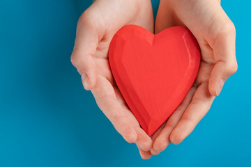 Hands of a teenager child holding a red wooden heart in their hands. Blue background
