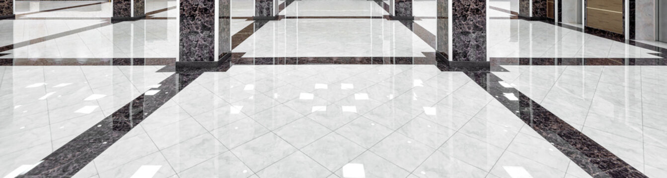 Marble floor of luxury lobby of company or hotel. Panorama of cleaned washed floor in corporate hallway. Shiny floor with reflections after professional cleaning. Care service of office interior.