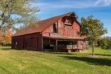 A beautiful, aging red barn in a rural area.