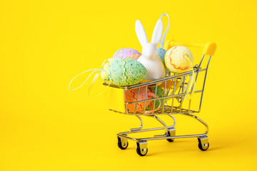 Happy Easter background.Easter eggs colorful in the shopping cart on bright yellow paper. Festive concept.Copy space for Text.