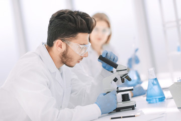 close up.male scientist sitting at a lab table.