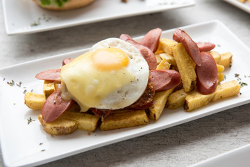 Salchipapas made of French fries and fried sausage, traditional fast food in South America, served on plates, mayonnaise, mustard and ketchup