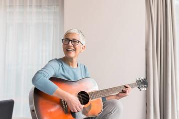 Smiling woman playing guitar