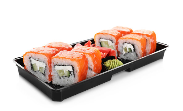 Box with tasty sushi rolls on white background. Food delivery