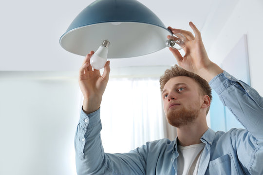 Man changing light bulb in pendant lamp indoors