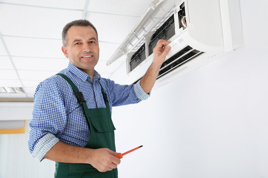 Electrician with screwdriver repairing air conditioner indoors