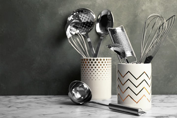 Holder with clean kitchen utensils on table. Space for text