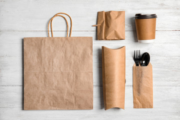 Different containers for mock up design on wooden background, flat lay. Food delivery service