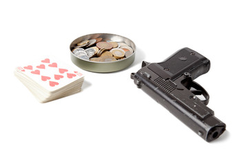 A deck of playing cards, columns of coins from different countries and a black pistol on a white isolated background