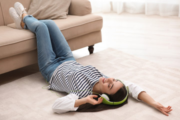 Young woman with headphones listening to music on floor in living room