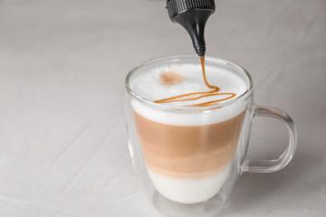 Adding caramel topping to latte macchiato on table