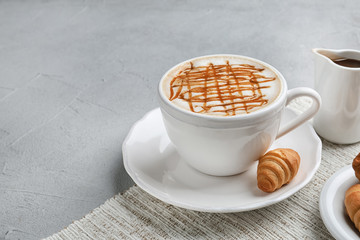 Cup of caramel macchiato with tasty pastry on table. Space for text