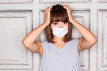 マスク・頭を抱える女性