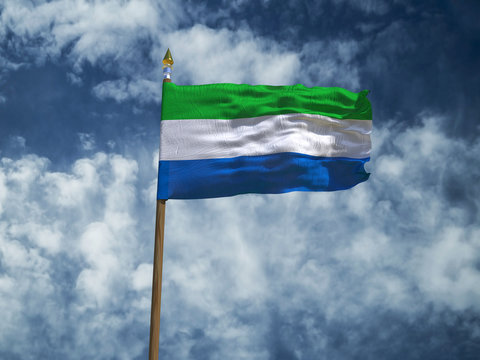Sierra Leone flag Silk waving flag of Sierra Leone made transparent fabric with wooden flagpole gold spear on background blue sky white smoke clouds real retro photo Countries of world 3d illustration