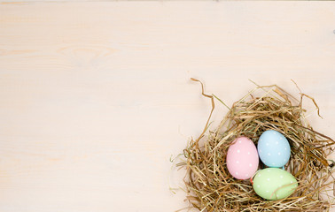 Clorful easter eggs in a natural straw nest. Top view. Empty space for text