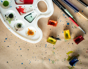Art palette with brushes and paint boxes on workshop table
