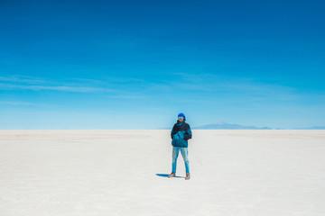 Tourist walking in sunshine Salar de Uyuni