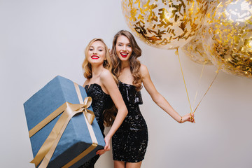 Two joyful fashionable young women in luxury black dresses celebrating birthday party on white background. Having fun, elegant look, smiling, true emotions. Holding present, golden balloons, tinsels