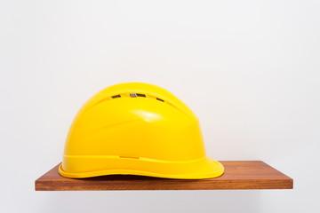 construction helmet on wooden shelf at white