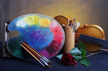 Attributes of the arts. Art palette, brushes, violin, red rose.