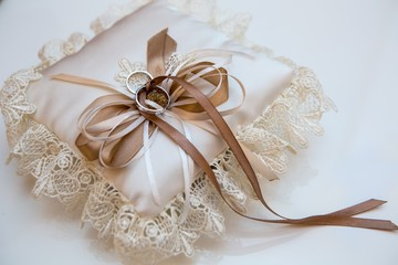 wedding accessory, embroidered lace pillow with rings of the bride and groom, still life in cream beige colors