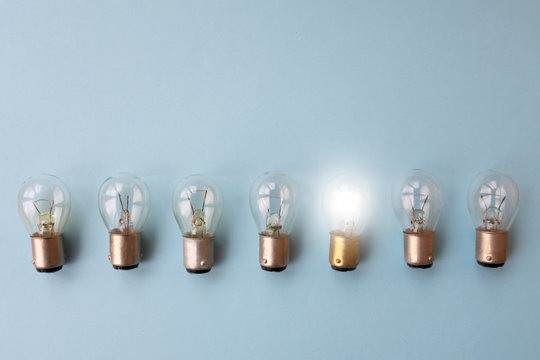 .Row of switched off light bulbs with one switched on. Concept of having idea and creativity