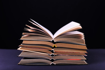 Open books are stacked on the desk, on a black background, isolate. Difficult homework at school, a mountain of knowledge.
