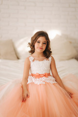 Little beautiful girl with brown hair in a Peach-colored dress. Girl sitting on the sofa