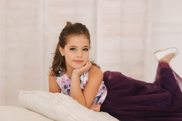 Happy child female in purple dress. Beautiful makeup and hairstyle