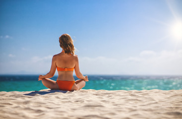 Wall Mural - woman practices yoga and meditates in lotus position on beach.