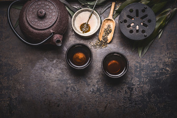 Traditional Asian green tea setting with teapot, cups, candle and honey on dark rustic background with copy space, top view
