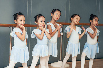 Choreographed dance by a group of young pretty Chinese young ballerinas practicing during class at a classical ballet school