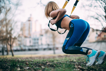 Young beautiful blonde woman using suspension straps in her exercise routine outdoors in the evening