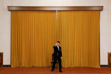 A security officer gestures at the photographer attempting to prevent taking pictures, as he keeps watch in a corridor of the Great Hall of the People during the Chinese People's Political Consultative Conference (CPPCC) in Beijing