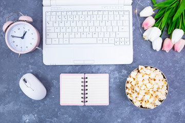 Notebook Notepad Alarm Clock Bouquet of tulips Popcorn in a bowl on the desktop